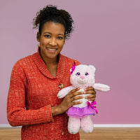 A woman holds a pink bear that is 12 inches tall while standing wearing a tutu