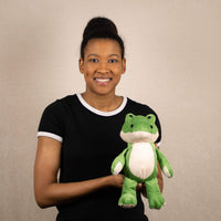 A woman holds a green alligator that is 9 inches tall while sitting