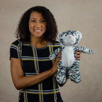 A woman holds a black and white stripped tiger that is 15 inches tall while standing