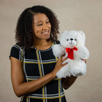A woman holds a white bear that is 11 inches tall while standing