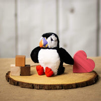 A puffin that is 7 inches tall while sitting on top of a piece of wood