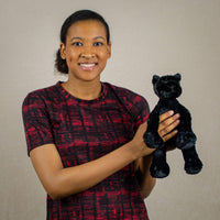 A woman holds a floppy black panther that is 12 inches tall while standing