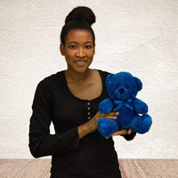 A woman holds a dark blue bear that's 9 inches tall while sitting