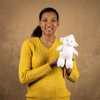 A woman holds a white lamb that rattles and is 10 inches tall while standing
