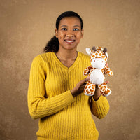A woman holds a spotted giraffe that rattles and is 10 inches tall while standing