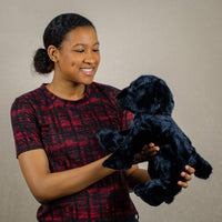 A woman holds a floppy black panther that is 12 inches from head to tail