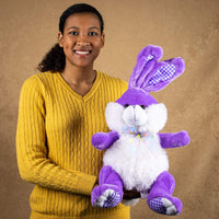 A woman holds a pastel purple bunny that is 14 inches tall while sitting