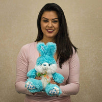 A woman holds a blue bunny that is 9 inches tall while sitting
