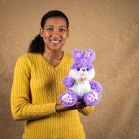 A woman holds a purple bunny that is 9 inches tall while sitting