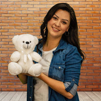 A woman holds a white bear that is 9 inches tall while sitting
