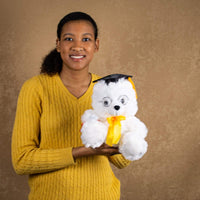 A woman holds a white grad bear that is 10 inches tall while standing
