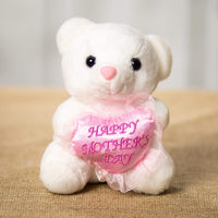 "A white bear that are 6 inches tall while sitting holding a pink heart that says ""Happy Mothers Day"""