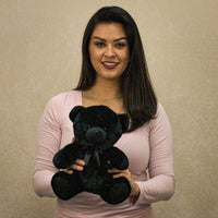 A woman holds a black bear that is 9 inches tall while sitting