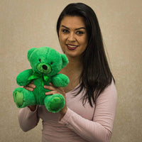A woman holds a green bear that is 9 inches tall while sitting