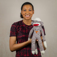 A woman holds  a brown UT sock monkey that is 18 inches tall while standing