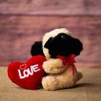 A pug that is 10 inches tall while sitting holding a red Love heart