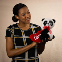 A woman holds a panda that is 10 inches tall while sitting holding a red Love heart