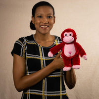 A woman holds a red monkey that is 10 inches tall while standing