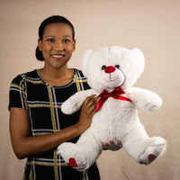 A woman holds a white bear that is 16 inches tall while sitting