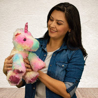 A woman holds a rainbow colored unicorn that is 11 inches tall while sitting