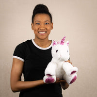 A woman holds a white unicorn that is 11 inches tall while sitting