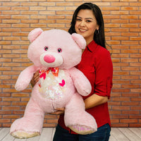 A woman holds a pink bear  that is 21 inches tall while sitting with a sequin belly and feet