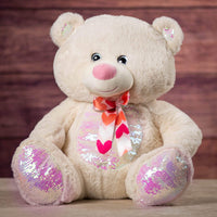 A cream bear that is 21 inches tall while sitting with a sequin belly and feet