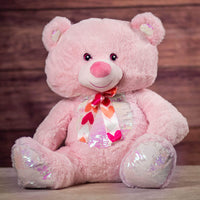 A pink bear that is 21 inches tall while sitting with a sequin belly and feet