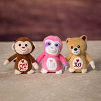 A brown monkey, and pink monkey and a beige bear that are 4 inches tall while sitting