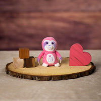 A pink monkey that is 4 inches tall while sitting on top of a piece of wood