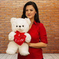 "A woman holds a white bear that is 18 inches tall while standing holding a red heart that says ""Love"""