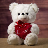 A large fluffy white bear holding a red heart that says Love