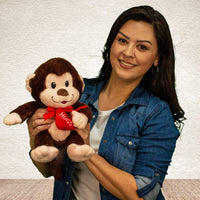 "A woman is holding a dark brown 10 inch from head to bottom sitting monkey with a red bow around its neck and is holding a red heart that says, ""HUGS"""