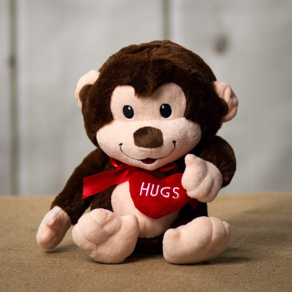 "A dark brown 10 inch from head to bottom sitting monkey with a red bow around its neck and is holding a red heart that says, ""HUGS"""