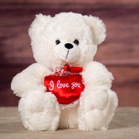 "A white bear that is 12 inches tall while sitting holding a red heart with white trimmings that says ""I Love You"""