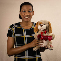 "A woman holds a singing/animated brown puppy holding red hearts that say ""I love you so much"""