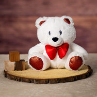 A white bear that is 8.5 inches tall while sitting on top of a piece of wood