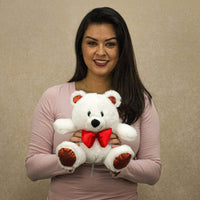 A woman holds a white bear that is 8.5 inches tall while sitting
