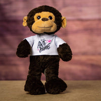 A brown monkey that is 15 inches tall while standing wearing a white shirt