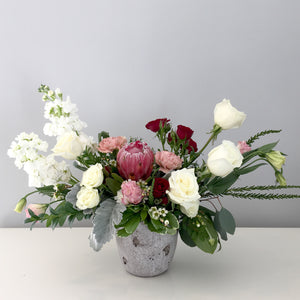 A beautiful red pink white flower arrangement featuring elegant blooms.