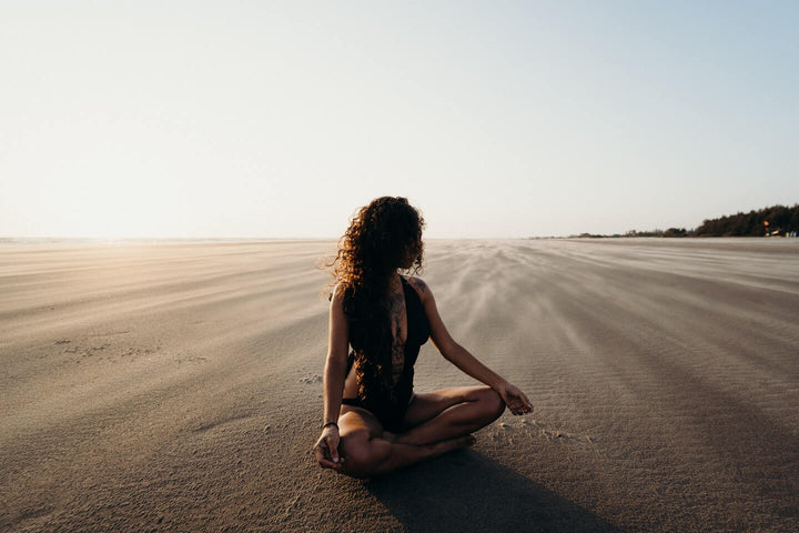 Yogini meditating on the beach in NZ
