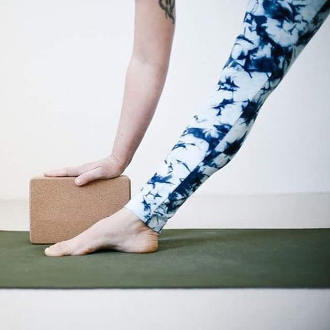 Yoga Teacher stretching with cork yoga block