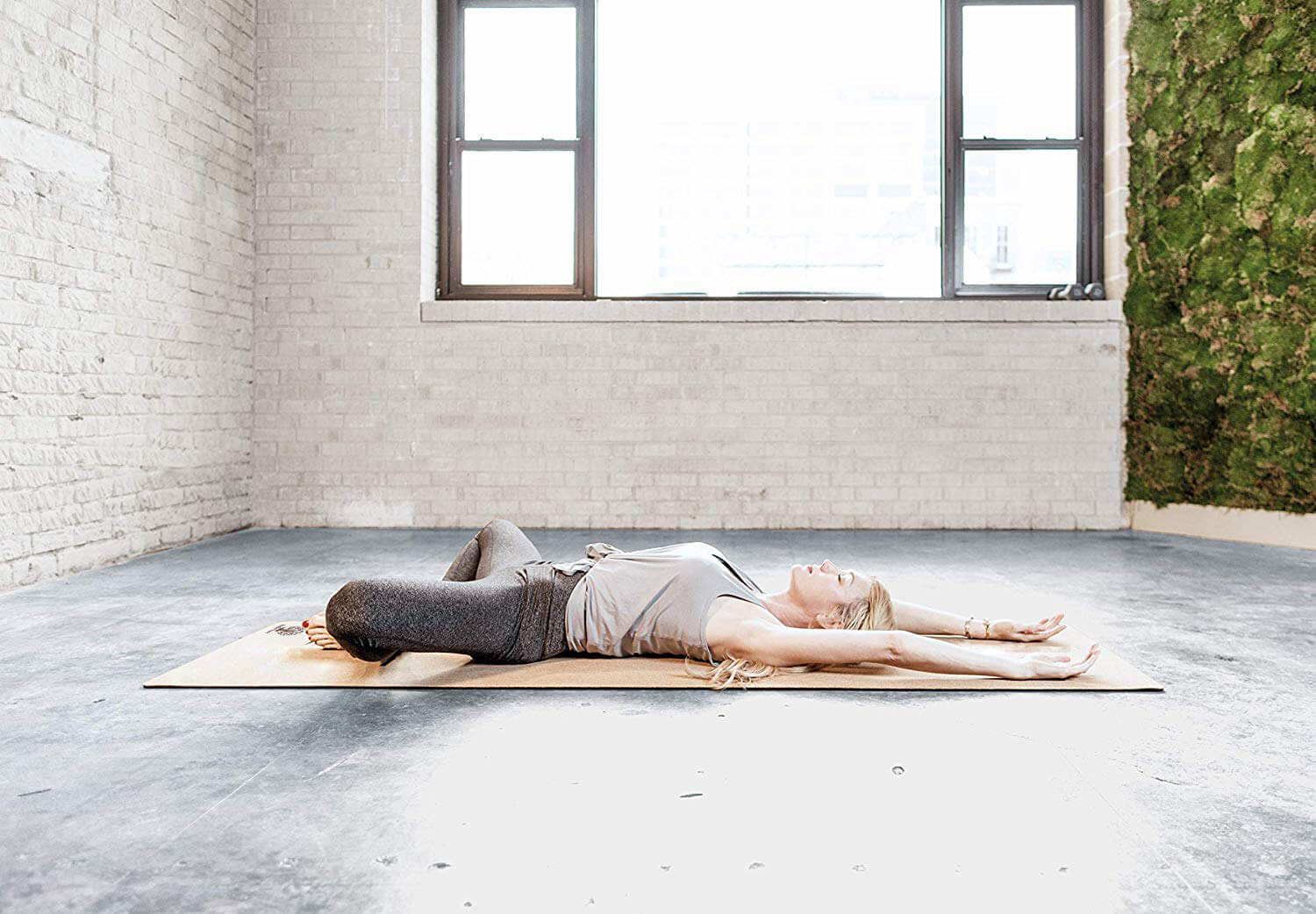Yogini in savasana on cork yoga mat