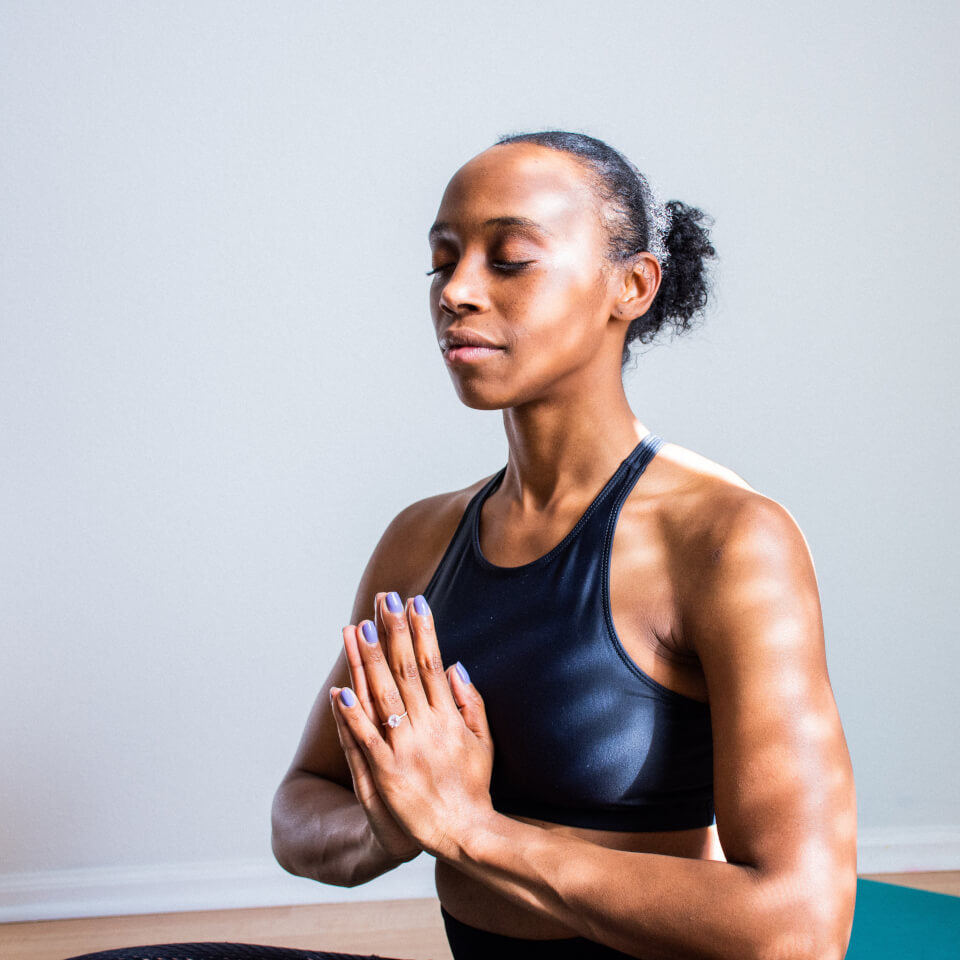 Woman sitting with eyes closed in Prayer Position