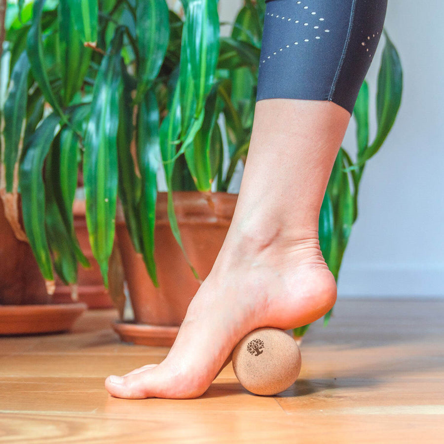 Massaging foot with cork massage ball