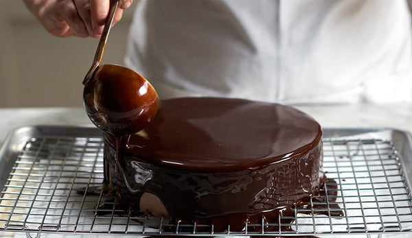 Chef Jacques Torres glazing cake with chocolate ganache
