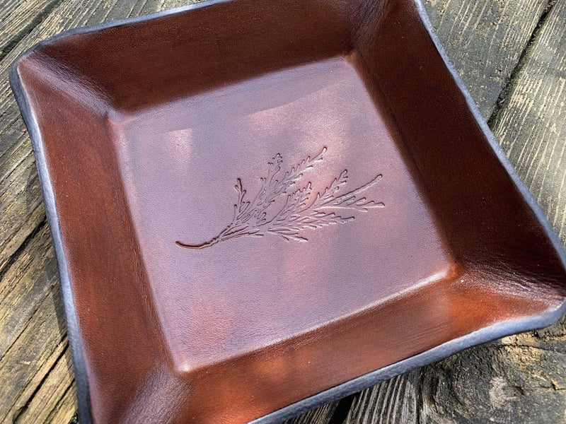 Dark brown leather tray with cedar leaf image. Detail.