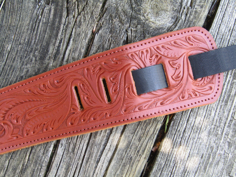 Tooled guitar strap with black end piece.