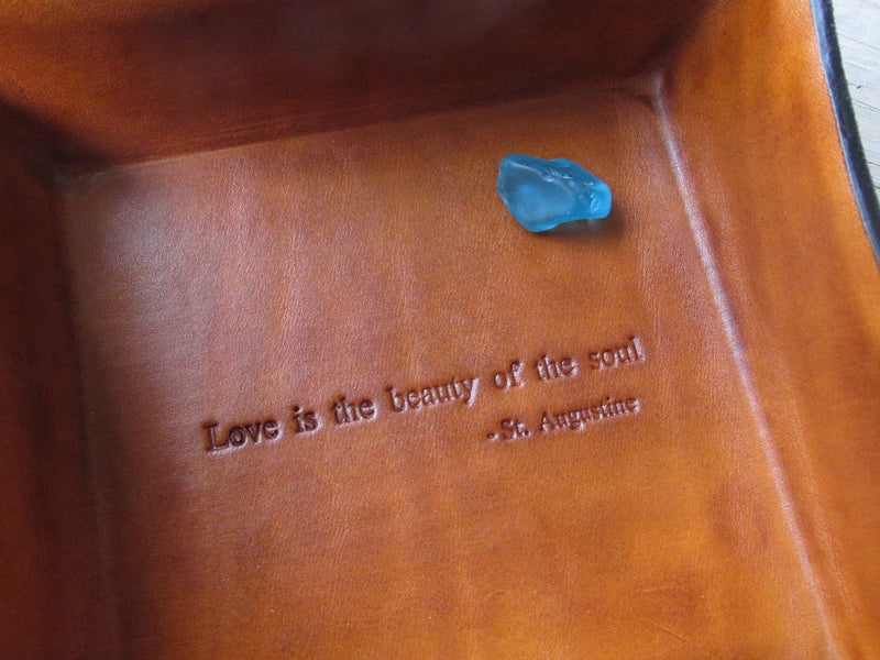 Detail of Twin Saints leather tray. St Augustine quote.
