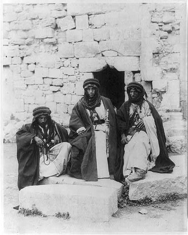 Three Bedouin men in front of wall; circa between 1910 to 1920
